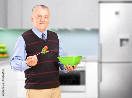 A mature man eating salad during a lunch
