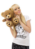 Pretty blonde girl wearing pajamas embraces teddy bear