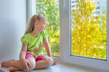 Cheerful girl sitting by the window