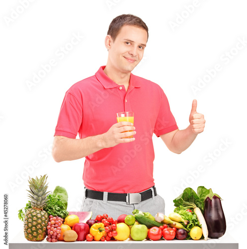 Guy holding a juice and giving thumb up with pile of food on a t
