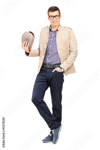 Full length portrait of a young man holding a hat