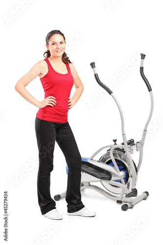 Young female posing next to a cross trainer