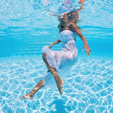 Underwater woman portrait with white dress in swimming pool.