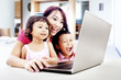Happy family with laptop at home