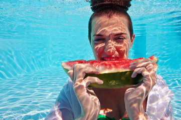 Underwater woman eating a slice of watermelon in swimming pool.
