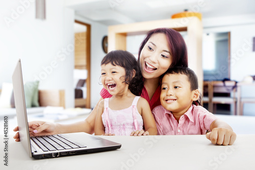 Happy family with laptop at home 1