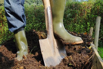 Mann beim Umgraben des Kompostes