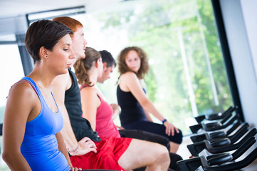 Five people tired in the gym, exercising their legs doing cardio