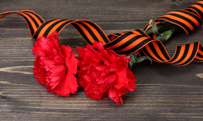carnations and St. George's ribbon on grey wooden background