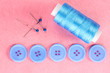 Colorful sewing buttons with thread on pink fabric