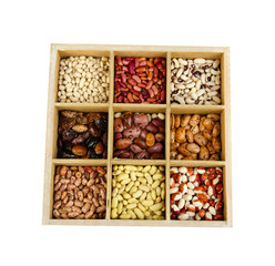 Diverse beans in wooden box sections isolated on white