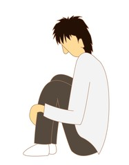 膝を抱える男性