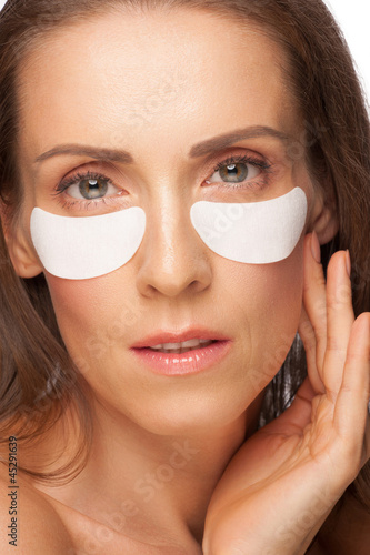 Woman applying gel eye mask