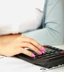 Businesswoman at her desk using a calculator