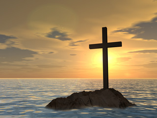 Conceptual cross on a rock in the sea at sunset