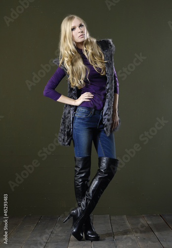 Full length fashion model in jeans posing wooden floor