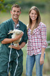 Smiling couple of duck breeders standing outdoors