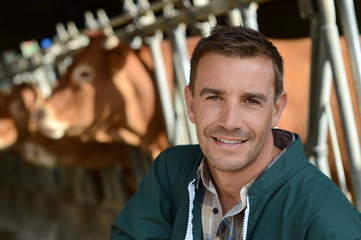 Portrait of smiling farmer with cows in background