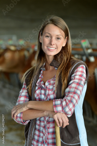 Smiling farmer woman standing in barn