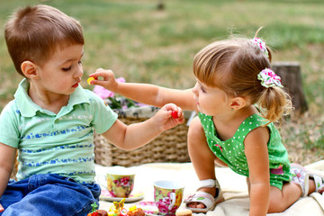 Caucasian little boy and girl eating sweets