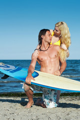 Young couple at the beach with surfboard.
