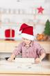 kleiner weihnachtsmann rollt teig aus