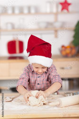 kleiner junge mit nikolausmütze knetet teig