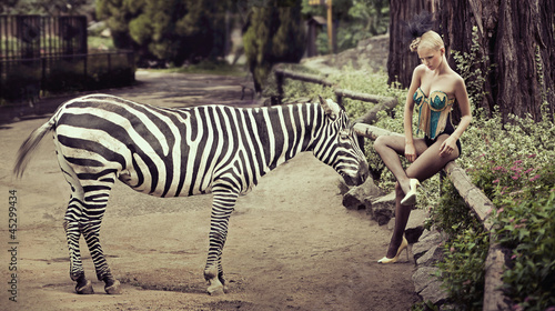 Beautiful lady sitting next to a zebra