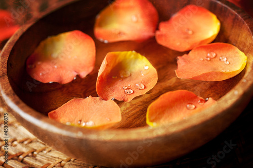 Close up of rose petals in a wooden bowl