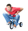 Man on a children's bicycle on white background