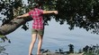 Girl jumps on a branch overwater