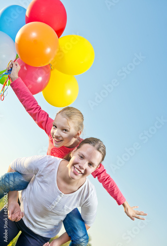 Two girls playing outside with balloons