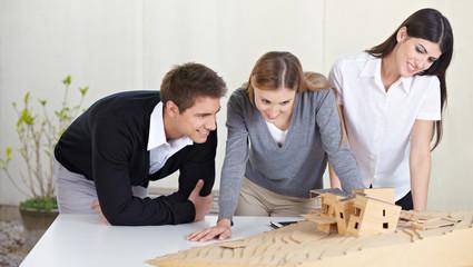 Architekten betrachten Modell eines Gebäudes