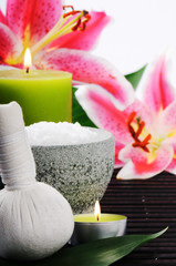Spa setting with sea salt, herbal ball and lily