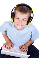 attracive kid is listening music with headphones and laptop