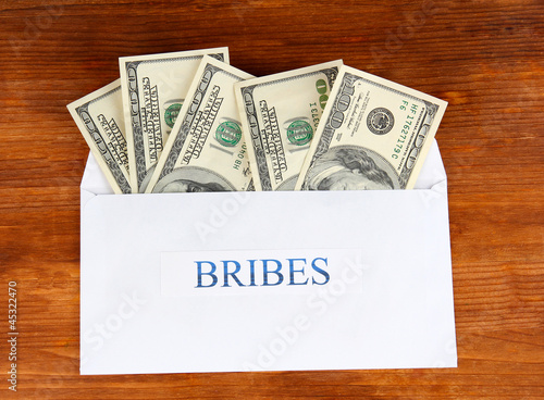 The envelope with the money bills on wooden background. Bribes.