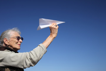 Senior woman playing with paper plane