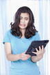 Teen girl looking with disgust at computer tablet in hand