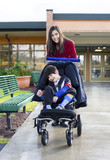 Fototapety Teenage girl pushing little disabled boy in wheelchair