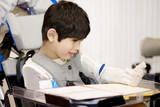 Fototapety Five year old disabled boy studying in wheelchair