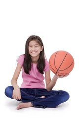 Young girl holding basketball, isolated on white