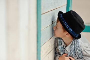 boy in black hat looks into the hole a wooden fence
