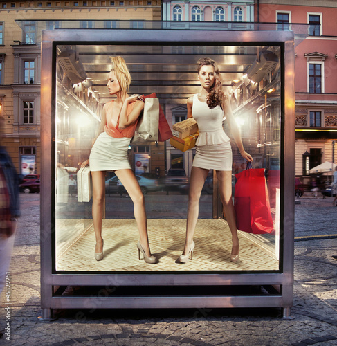 Two shopping women on exhibition window
