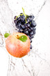 Juicy red apple and bunch of grapes in water splash isolated on