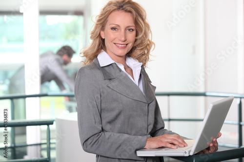 blonde businesswoman all smiles with laptop