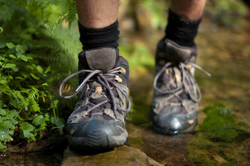 Closeup of hiking boots over a stream
