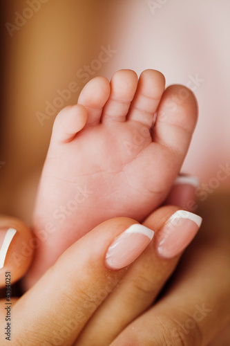 newborn baby foot on female hands