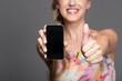 Frau zeigt mit Smartphone