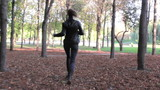 Young woman runs on park. Steadycam