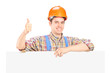 Happy male construction worker posing behind a panel giving thum
